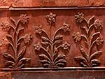 Intricate carved flowers in the red sandstone