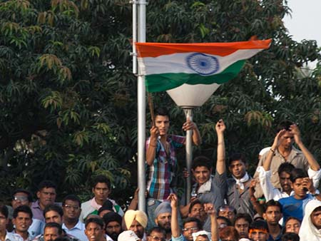 Patriotic Indian boy waving a large Indian flag