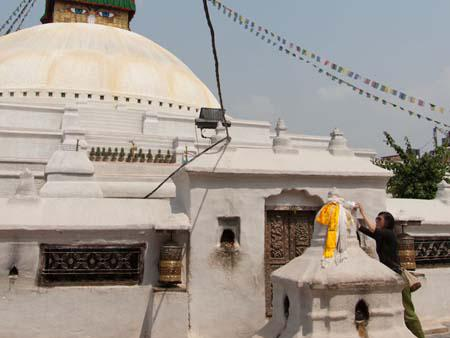 Sonya tying a white scarf to a smaller stupa in front of the Bodhnath Stupa