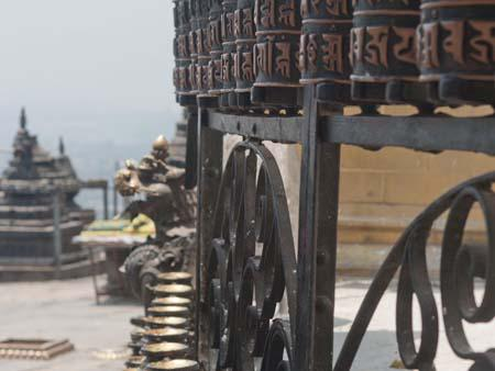 The prayer wheels and oil candles surrounding the large stupa